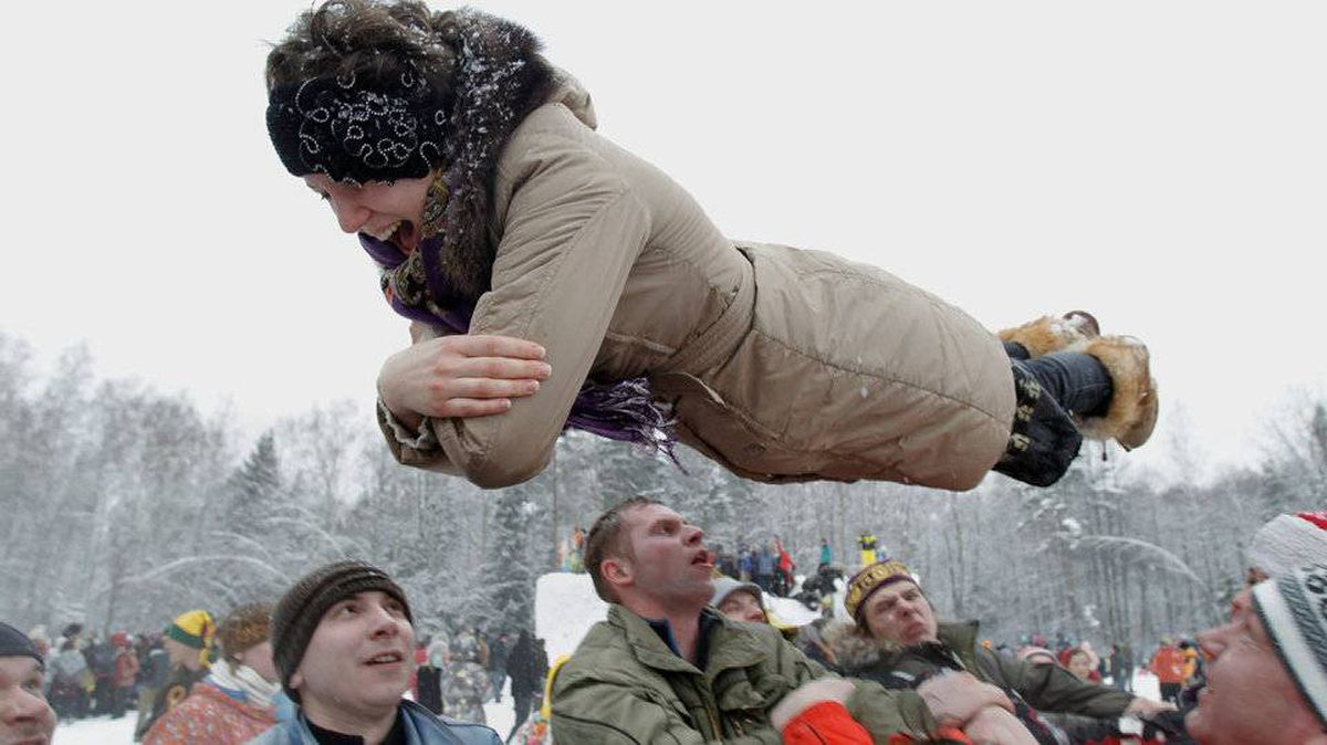 A woman is thrown in the air as she and others have fun enjoying celebrations of Maslenitsa. The traditional Russian holiday marking the end of winter dates back to pagan times.