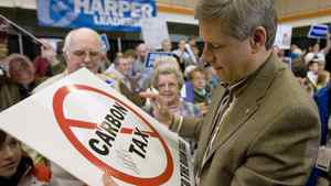 "Stephen Harper signs a ""No Carbon Tax"" sign at a campaign rally in Cornwall, P.E.I. on Oct 13, 2008. Mr. Harper's government is facing growing calls for a carbon tax from some surprising quarters as it pursues plans to regulate industrial sources of greenhouse-gas emissions."