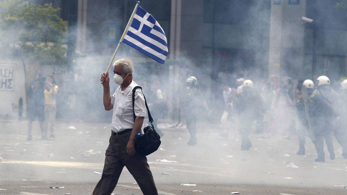 A protester holds a Greek flag as he walks in tear gas outside of the Greek Parliament in central Athens, during a rally against plans for new austerity measures, on Wednesday, June 15, 2011. A 24-hour strike by Greece's largest labor unions is set to cripple public services Wednesday, as the Socialist government begins a legislative battle to push through last-ditch cost cutting reforms that will exceed its own term in office. Demonstrators had camped outside parliament since May 25, 2011.