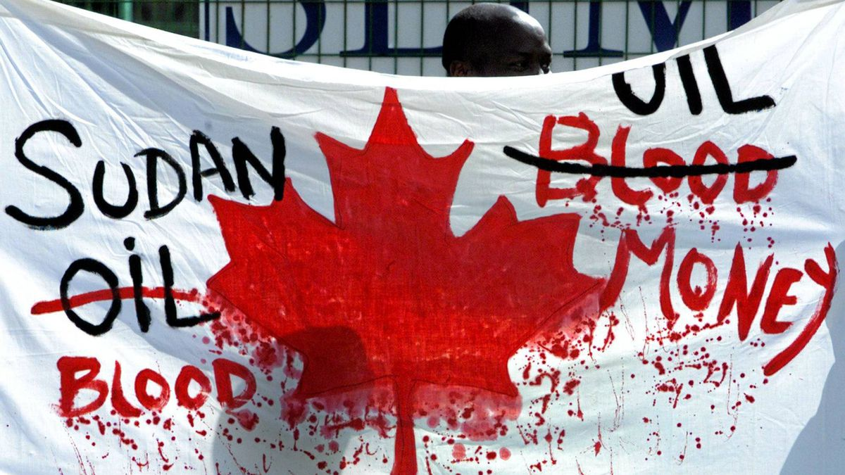 A Sudanese demonstrator casts his shadow onto a protest banner outside the Talisman Energy Annual General Meeting in Calgary, Wednesday May 1, 2002.