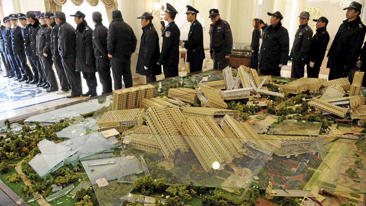 Police officers in Hangzhou maintain order after a model of a new housing estate was smashed by property owners upset that the asking price of new homes in the complex had been cut dramatically, making their own homes worth a lot less.