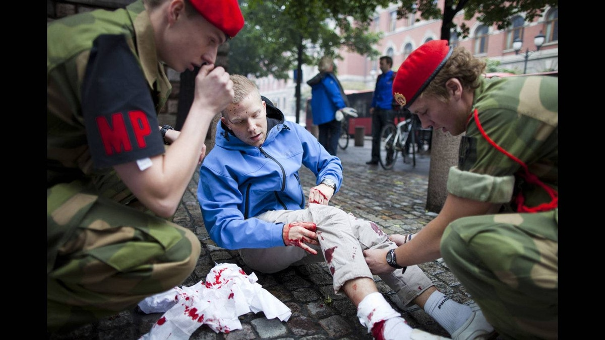 An injured man is treated at the scene after an explosion near the government buildings in Norway's capital Oslo on July 22, 2011. At least one person was killed by the powerful explosion which ripped through government and media buildings.