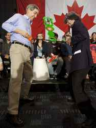 "The Liberals went negative in their television advertising this weekend with an ad campaign claiming Conservative promises to scale back government spending will ultimately result in cuts to health care. ""Where would Harper's cuts leave your family's health,"" the narrator asks. ""The stakes are too high. Vote Liberal."" Liberal Leader Michael Ignatieff continued with the health-care message at a rally in Edmonton with the help of former Prime Minister Paul Martin who criticized the Conservatives for numbers in the party's platform that were different than those in the budget just a few weeks earlier. On Sunday Mr. Ignatieff and Mr. Martin were in Vancouver where the Liberal Leader promised to hold a First Ministers meeting on health care with the provinces and territories. He also brushed off Mr. Harper's claims that only a Conservative majority can prevent the country from breaking apart. (Photo: Mr. Ignatieff, left, does the hip flick game with comedian and self-proclaimed 'guerilla journalist' Nardwuar)"