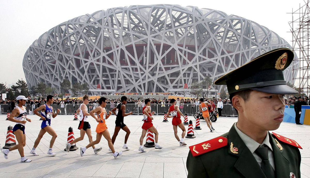 "Chinese paramilitary police stands guard as athletes walk past the Olympic National Stadium ""Bird Nest"" during the Race Walking Challenge in Beijing, China, Friday, April 18, 2008. The race walking is the first event held at the National Stadium, ahead of the Olympic Games this August. (AP Photo/Andy Wong)"