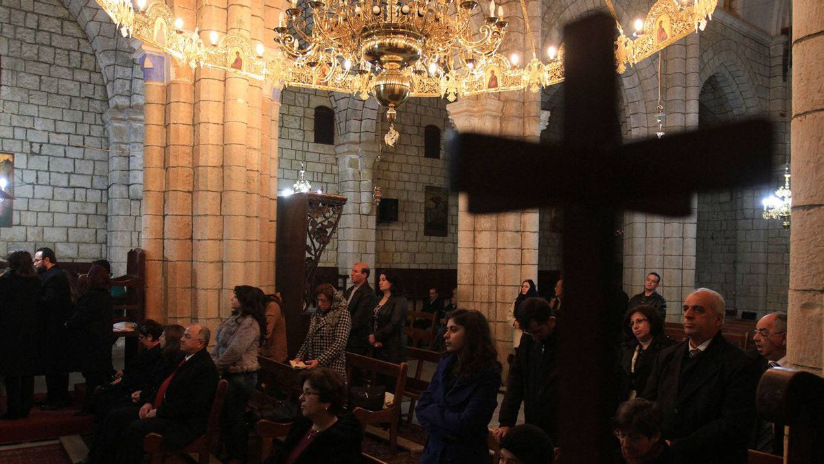 """Syrian Christians attend Christmas Day mass at the Saint George Monastery in Mishtaya, some 50 km from Homs, on December 25, 2011. Escaping a city wracked by incessant violence, Syrian Christians from Homs flock to a nearby monastery to celebrate Christmas away from a place that has """"lost its senses."""""""