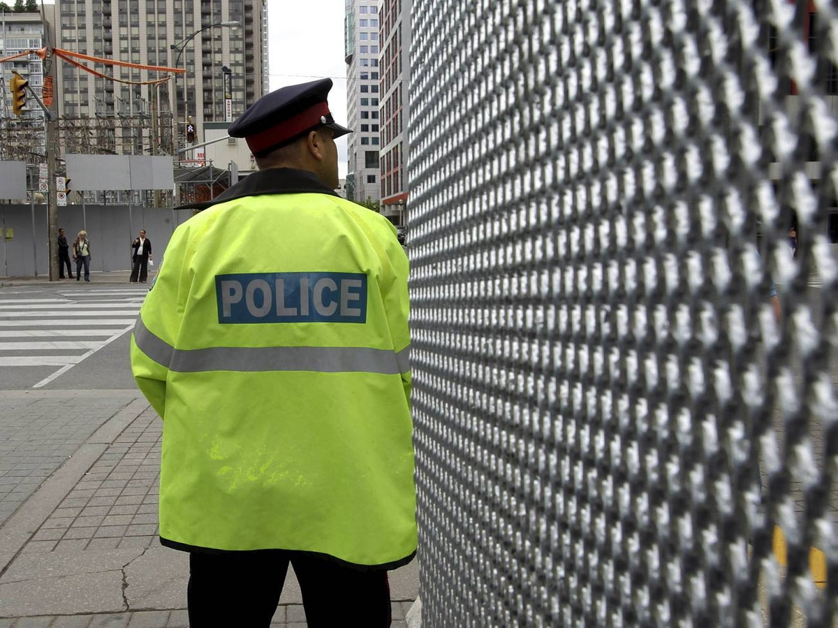 A police officer stands near security fence for the June 26-27 G20 Summit in Toronto.