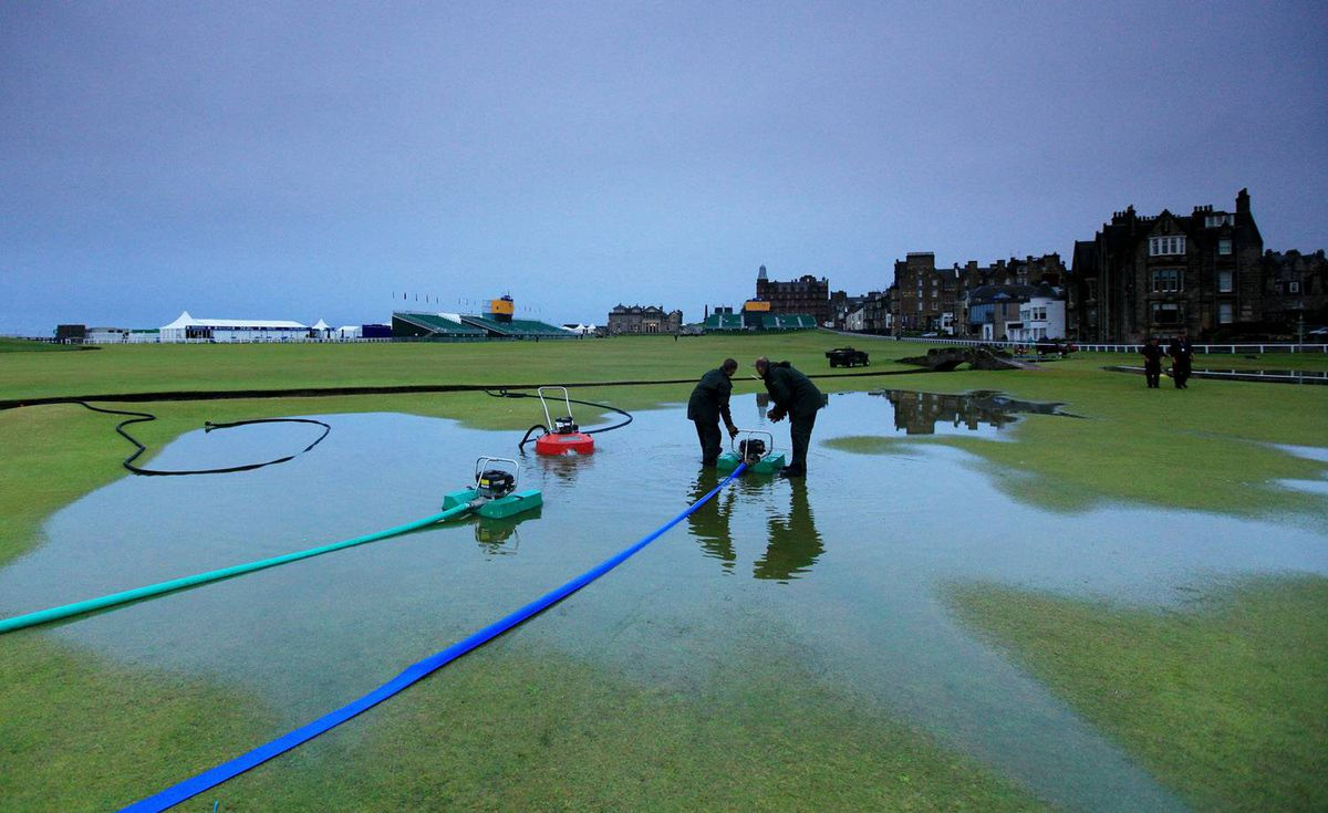 Course workers clear water which has pooled on the 1st and 18th greens