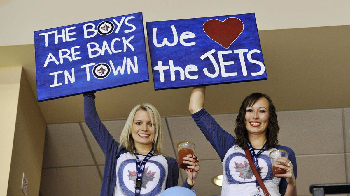 Winnipeg Jets fans cheer as their team plays the Montreal Canadiens during the first period of their NHL hockey game in Winnipeg, Oct. 9, 2011.