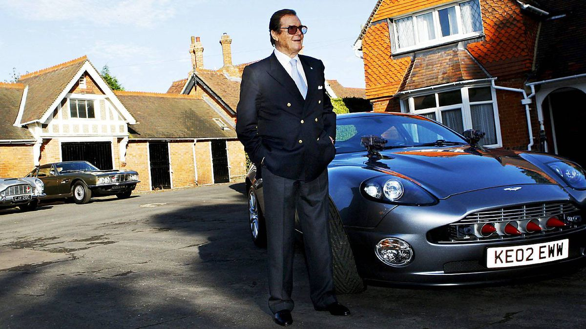 British actor Roger Moore stands beside an Aston Martin in 2008. Moore played James Bond in seven films from 1973 to 1985.