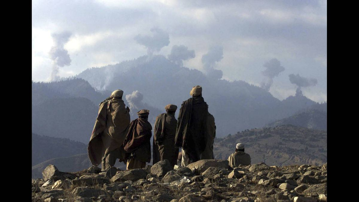 Anti-Taliban Afghan fighters watch several explosions from U.S. bombings in the Tora Bora mountains in Afghanistan, December 16, 2001.