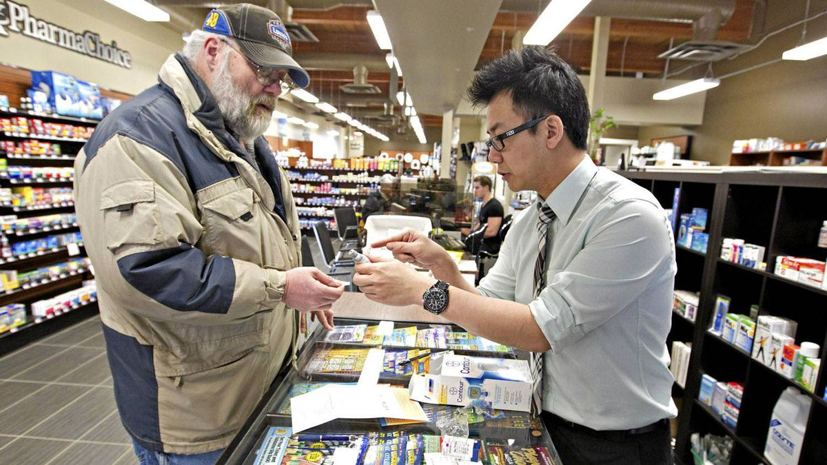 Kit Poon, owner of Main Street Home Health Pharmacy in Stony Plain, helps customer Randy Ulmer with a blood glucose monitoring device.