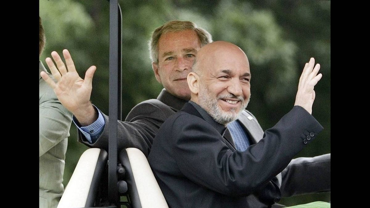 U.S. President George W. Bush (L) and Afghanistan's President Hamid Karzai wave from a golf cart after Karzai's arrival at the Presidential retreat, Camp David, outside of Thurmont, Maryland, for a two-day visit, August 5, 2007.