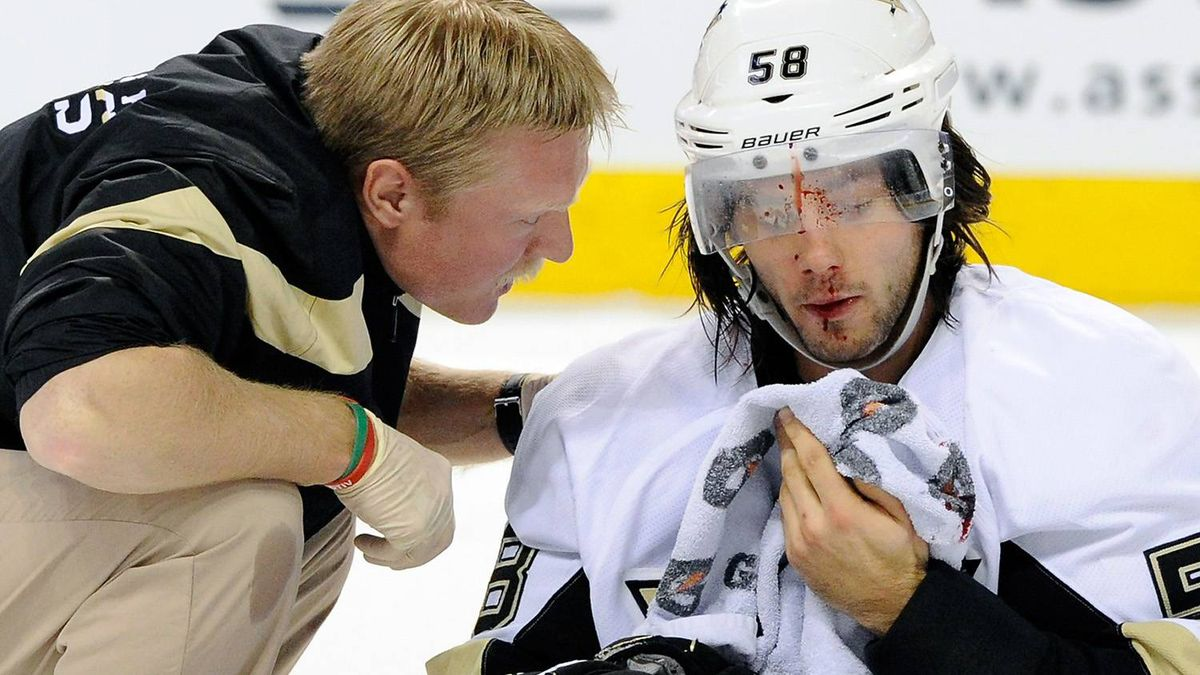Kris Letang #58 of the Pittsburgh Penguins is tended to by Pittsburgh Penguins staff after being hit by Max Pacioretty #67 of the Montreal Canadiens (not pictured) during the NHL game at the Bell Centre on November 26, 2011 in Montreal, Quebec, Canada. The Penguins defeated the Canadiens 4-3 in overtime. (Photo by Richard Wolowicz/Getty Images)