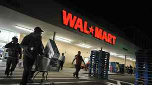 Shoppers wheel their purchases out of a Wal-Mart store in Los Angeles, Calif.