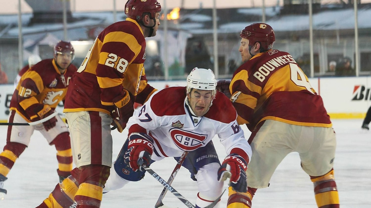 Max Pacioretty #67 of the Montreal Canadiens squeezes past Robyn Regehr #28 and Jay Bouwmeester #4 of the Calgary Flames during the 2011 NHL Heritage Classic Game at McMahon Stadium on February 20, 2011 in Calgary, Alberta, Canada. (Photo by Mike Ridewood/Getty Images)