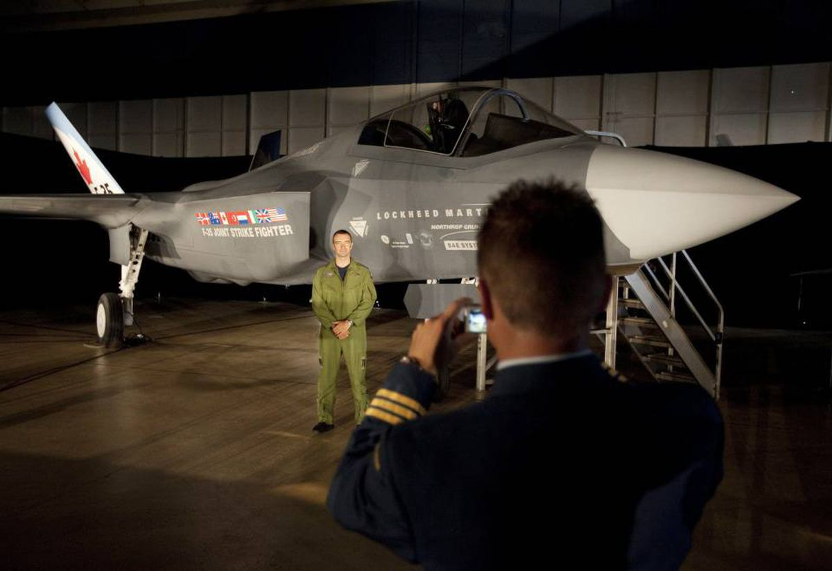 A Canadian Forces pilot has his picture taken in front of a F-35 Strike Fighter mock-up before a news conference in Ottawa on July 16, 2010.