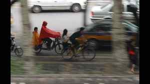 This photo of traffic in Beiijng was shot at 1/15 of a second. The lens was panned - moving at the same speed as the child in yellow and the adult in red. Thus they appear sharp. All else will appear to blur.