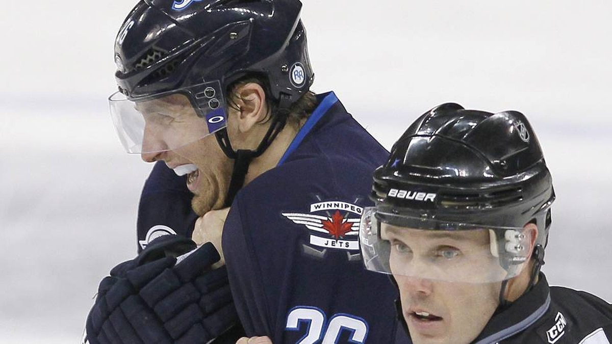 Winnipeg Jets' Blake Wheeler is escorted to the bench after getting hit in the throat with a shot from the point during second period NHL action aginst the New Jersey Devils' in Winnipeg on Saturday.