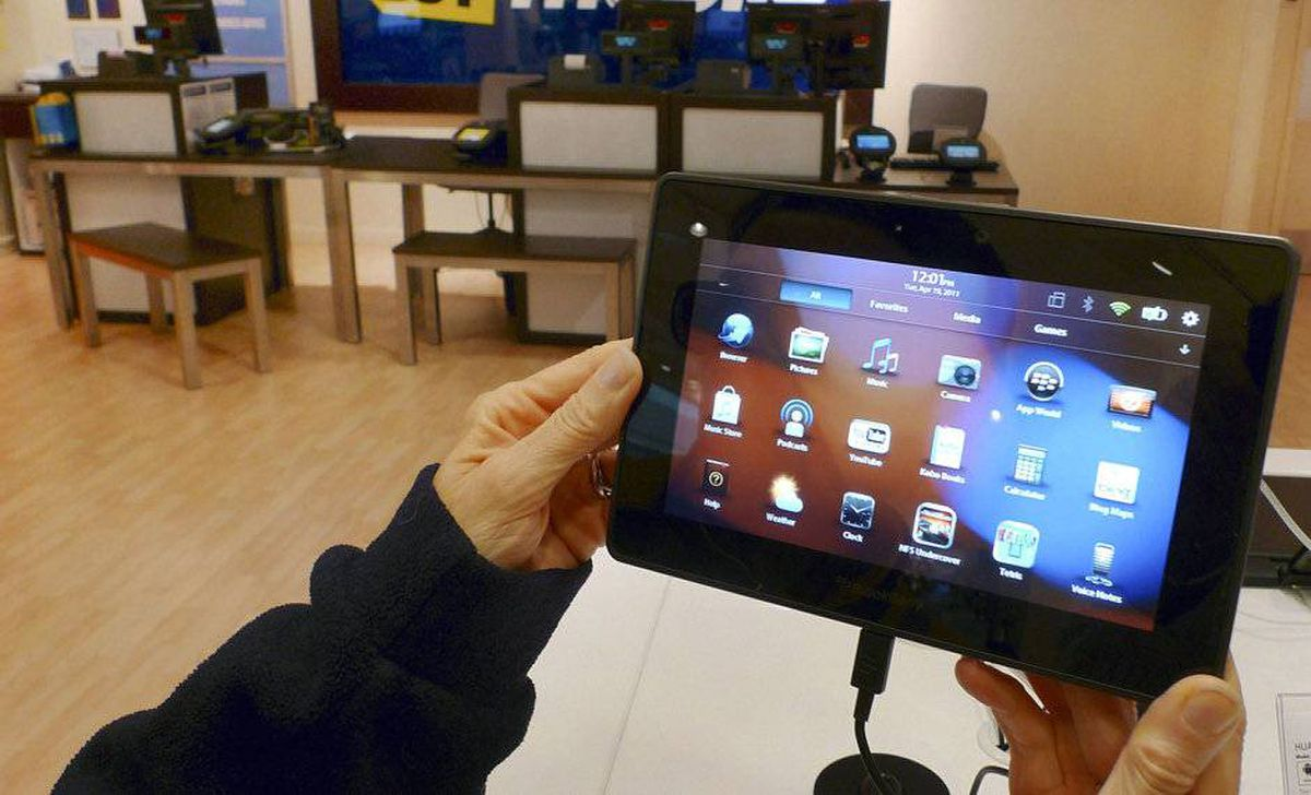 A customer holds a Research In Motion's PlayBook tablet computer.