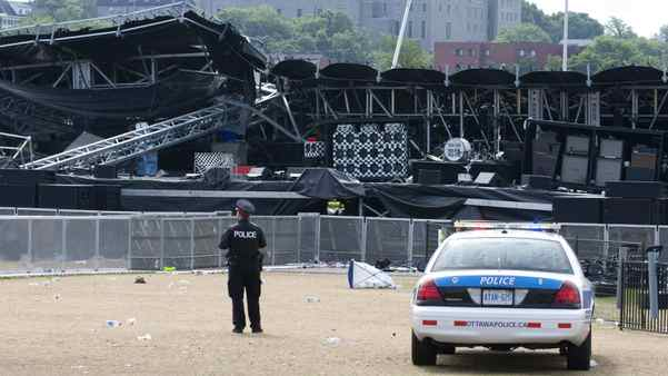A police officer watches over the Ottawa Bluesfest's collapsed main stage in Ottawa, Monday July 18, 2011.
