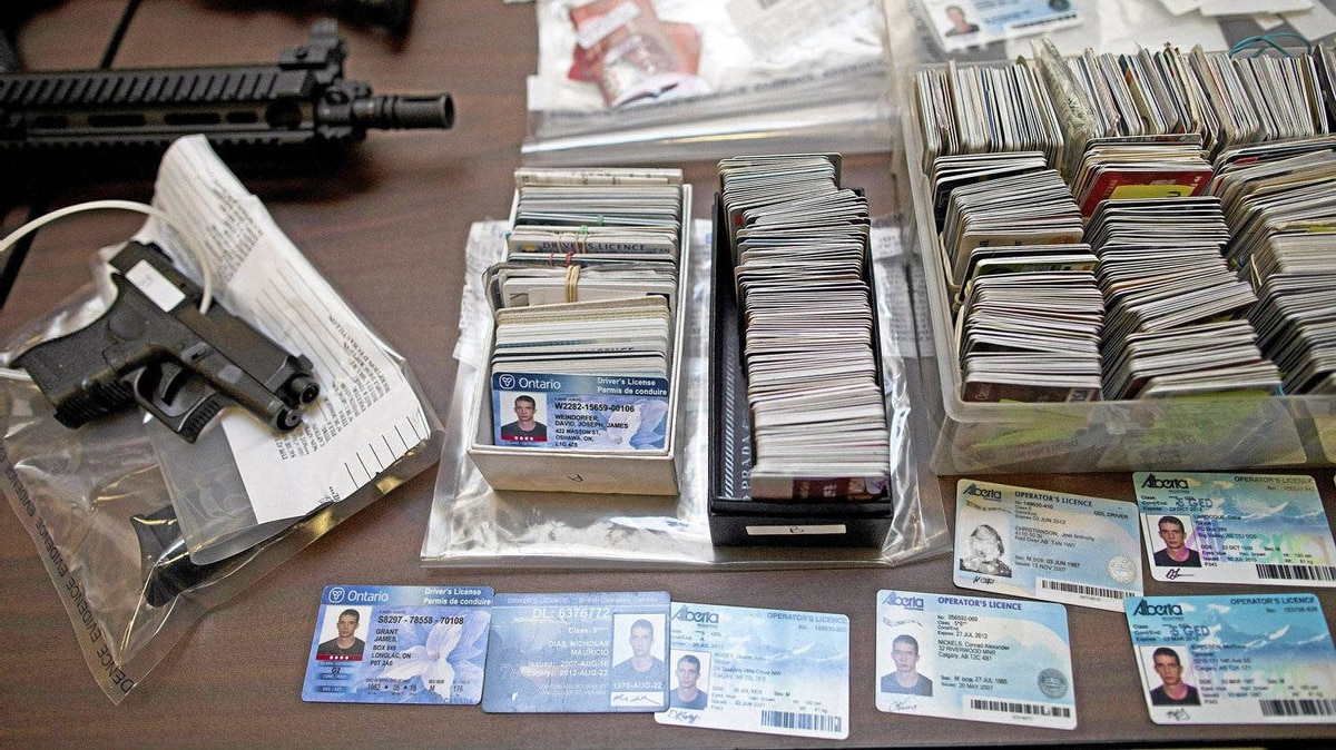 Fake identification, credit cards and replica weapons are presented at a news conference in Burnaby, B.C., on Tuesday, March 20, 2012, after they were seized in a March 7 raid.