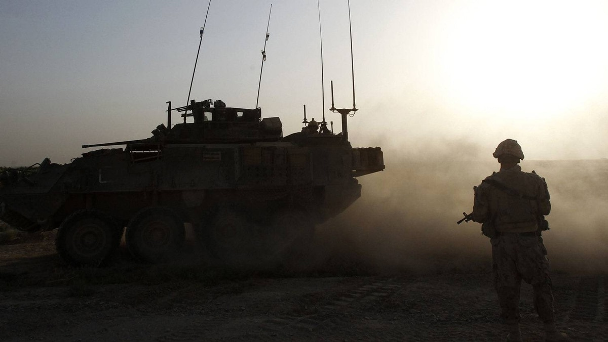 A Canadian light armored vehicle drives next to a soldier from Bulldog Company, 1st Battalion, 22nd Royal Regiment, walks during a patrol in the Panjwai district of Kandahar province southern Afghanistan June 25, 2011.
