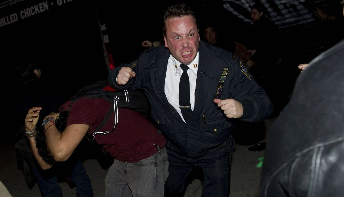 A New York City police officer scuffles with Occupy Wall Street protesters after they were evicted from Zuccotti Park on November 15, 2011 in New York.