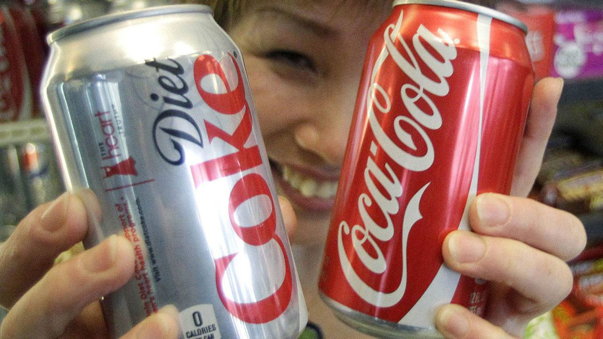 Jane Choi holds cans of Coca-Cola and Diet Coke in Anne's Deli, in Portland, Ore.