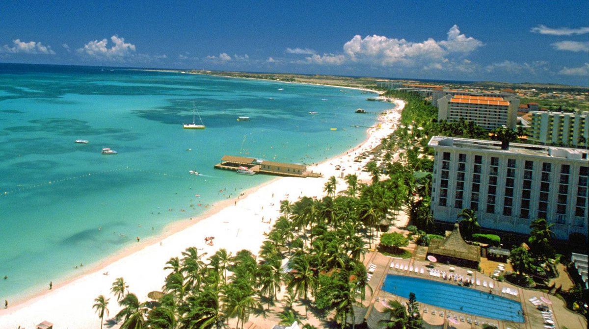 Enjoy a sunny holiday at Palm Beach in Aruba.