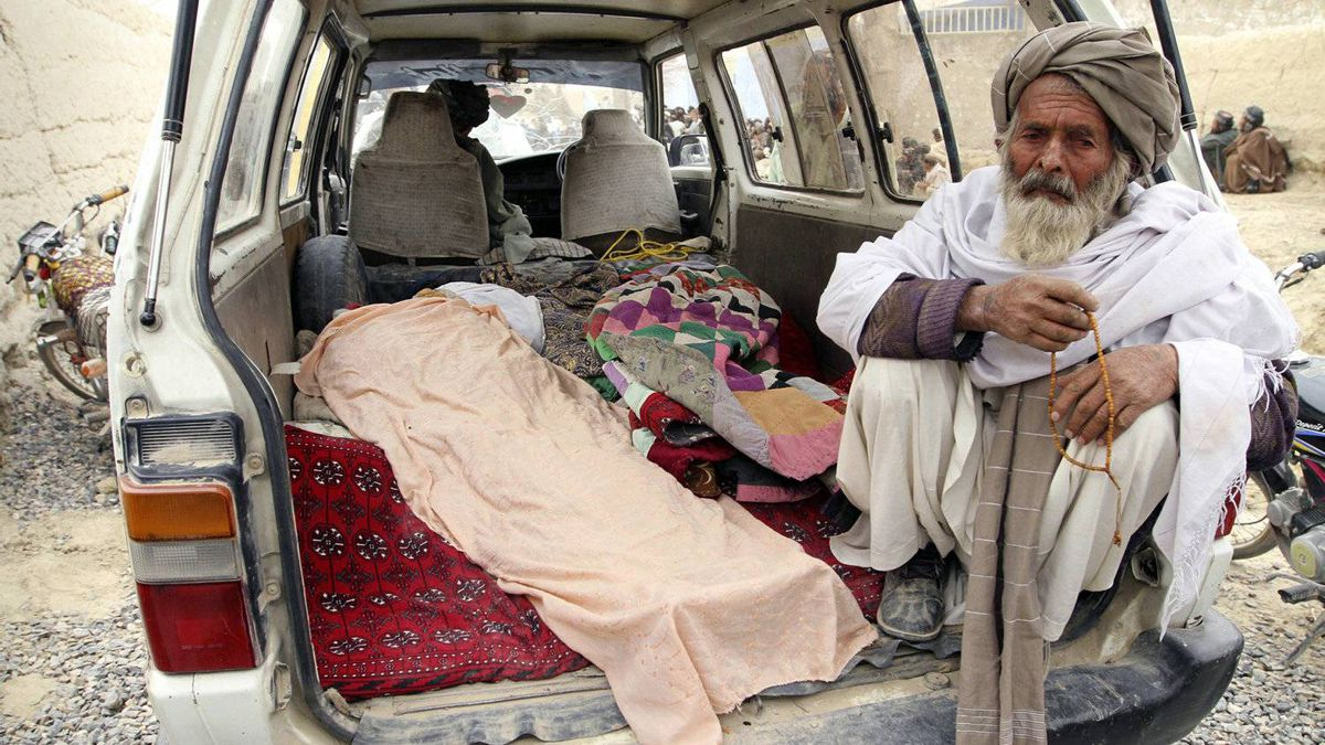 An elderly Afghan man sits next to the covered body of a person who was allegedly killed by a U.S. service member in Panjwai, Kandahar province south of Kabul, Afghanistan, Sunday, March 11, 2012.