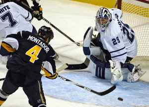 Toronto Maple Leafs goalie Joey MacDonald, right, watches Buffalo Sabres defenceman Steve Montador shoot the puck during a preseason NHL hockey game in Buffalo, N.Y., on Wednesday, Sept. 23, 2009.