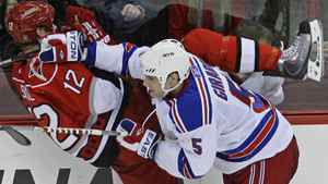 Carolina Hurricanes' Eric Staal (12) is checked against the boards by New York Rangers' Dan Girardi (5) during the third period of an NHL hockey game in Raleigh, N.C., Tuesday, Feb. 22, 2011. New York won 4-3 in a shootout. (AP Photo/Gerry Broome)
