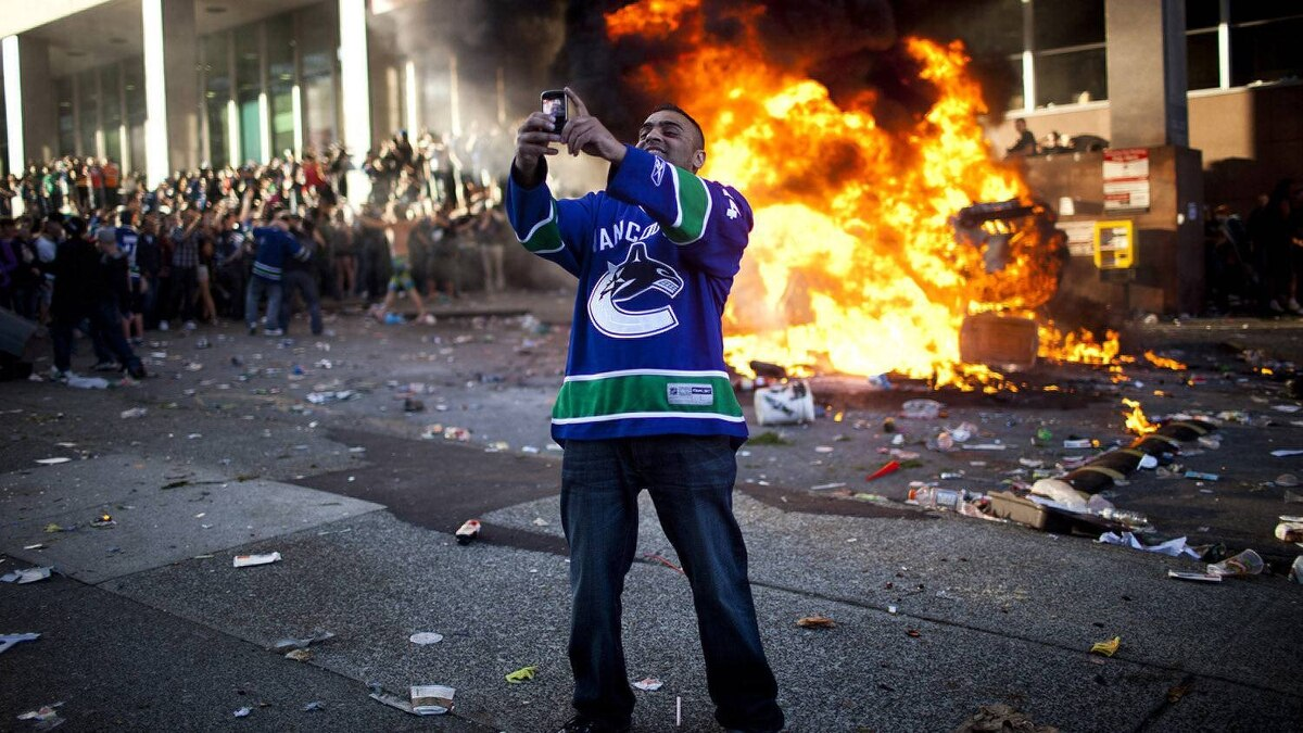 A Canucks fan takes a picture of himself in front of a burning car at the corner of Hamilton Street and Georgia Street after the Bruins won the Stanley Cup in Vancouver.
