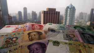 Different values of China's yuan banknotes are placed on a window sill as Shanghai's skyscrapers are seen in the background, in this April 15, 2012 file photo illustration taken in Shanghai. China's central bank cut benchmark interest rates by 25 basis points on June 7, 2012 in a surprise move to shore up slackening economic growth, its first rate cut since the depths of the 2008/09 financial crisis.