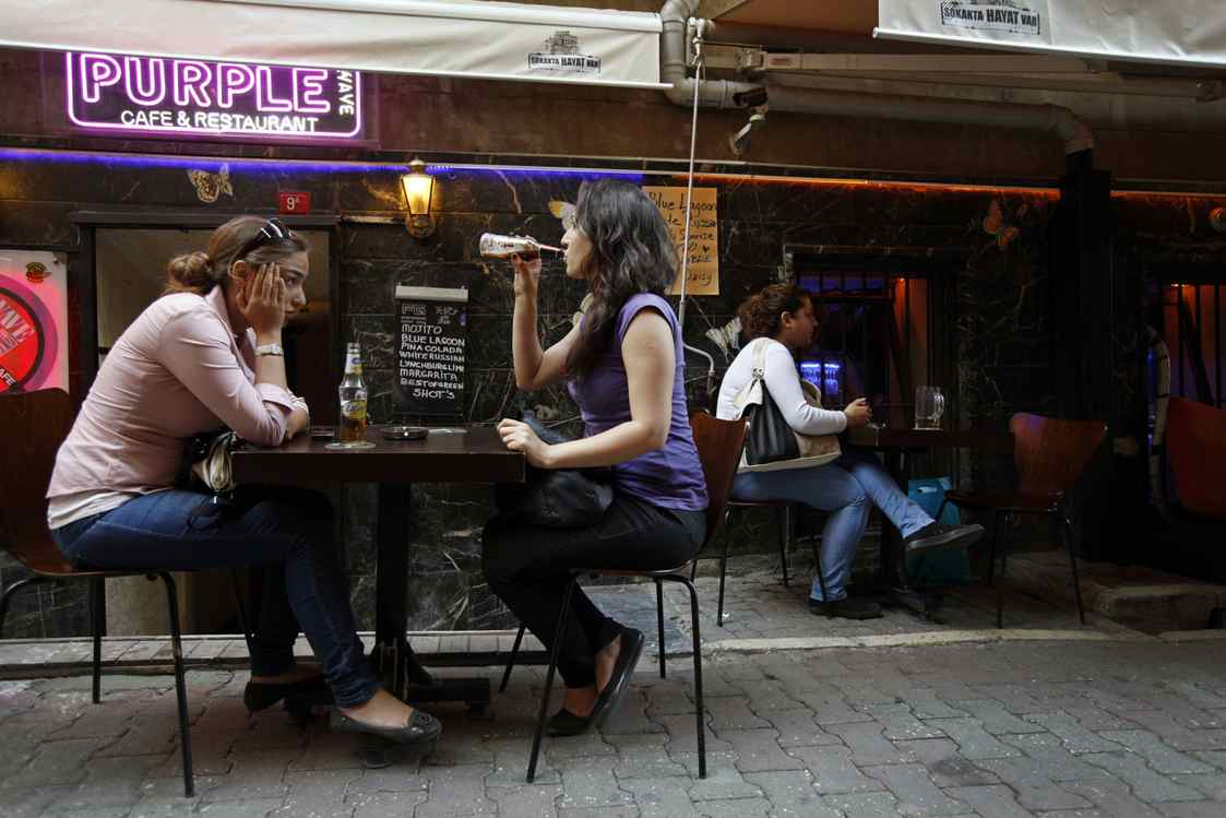 Patrons sit outside a bar in Beyoglu, in the heart of Istanbul, where authorities have banned tables and chairs in the street since mid-July.