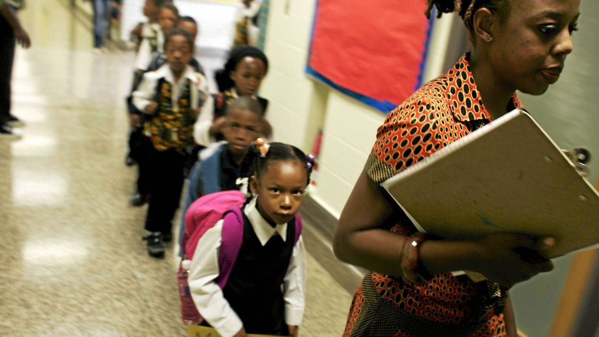 Grade one teacher Nadia Hohn escorts her students to class at The Afrocentric alternative school opened in Toronto, Ontario on September 8, 2009