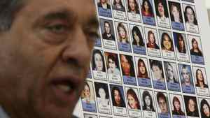 Photographs of missing women are displayed as Commissioner Wally Oppal speaks during the Missing Women Commission of Inquiry public forum in Vancouver on Wednesday Jan. 19, 2011.
