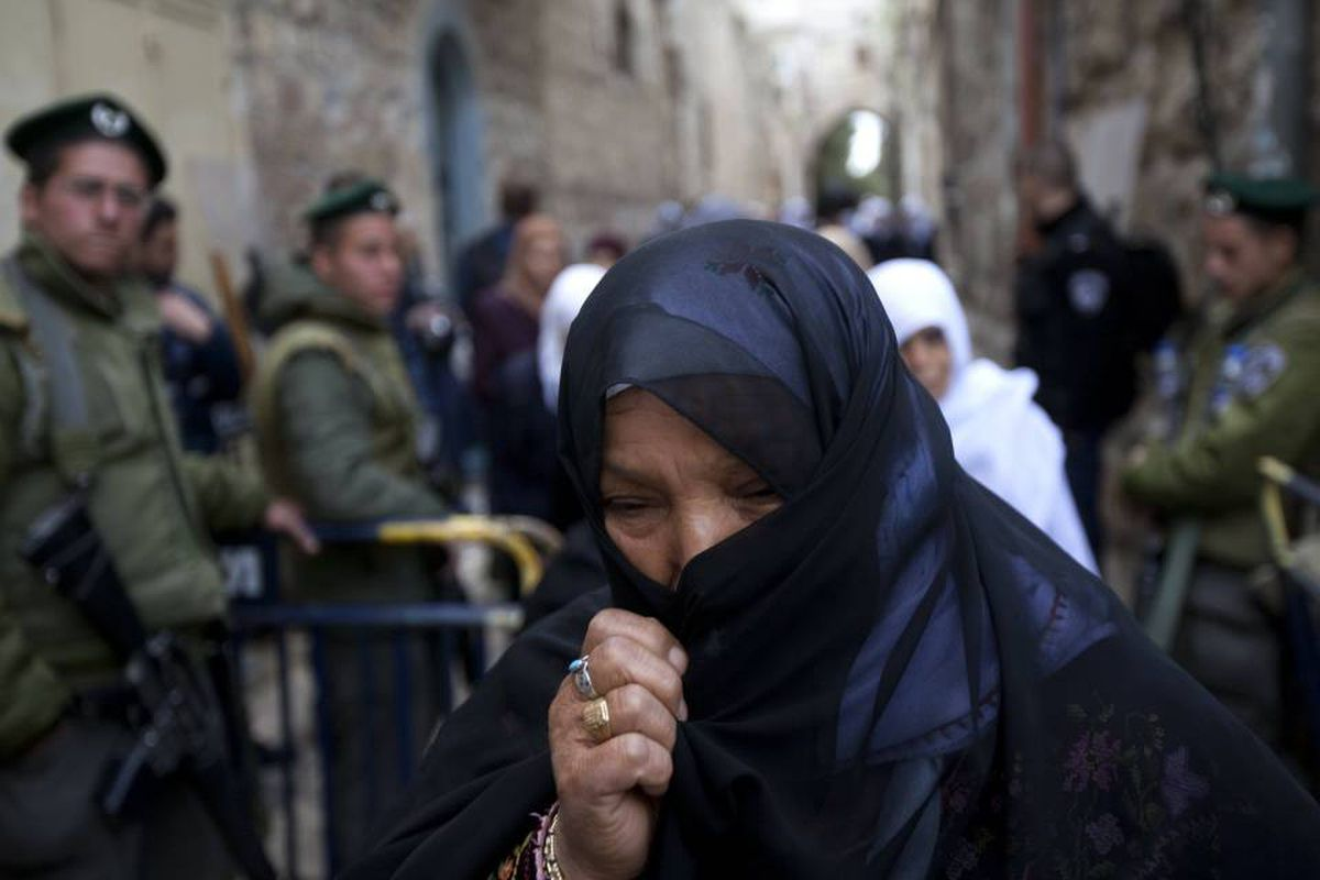 A Palestinian woman passes by Israeli border policemen on guard in Jerusalem's Old City in March.