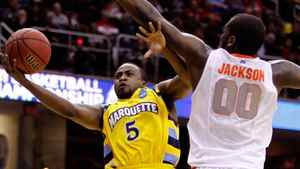 Junior Cadougan #5 of the Marquette Golden Eagles drives to the basket against Rick Jackson #00 of the Syracuse Orange during the third of the 2011 NCAA men's basketball tournament at Quicken Loans Arena on March 20, 2011 in Cleveland, Ohio.