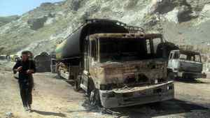 A Pakistani policeman walks past the wreckage of charred NATO supply oil tankers after a bomb blast in the Torkham area of the troubled Khyber tribal region near the Afghan border on May 14, 2011. At least seven NATO oil tankers bound for Afghanistan caught fire on late May 13 after a bomb planted beneath one of them exploded, but there were no casualties, officials in Pakistan said.