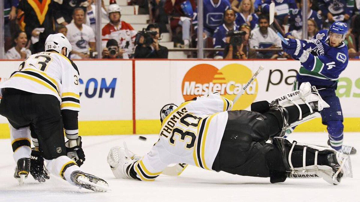 Boston Bruins goalie Tim Thomas dives for a puck shot by Vancouver Canucks' Alex Burrows as Boston Bruins defenceman Zdeno Chara covers the net.