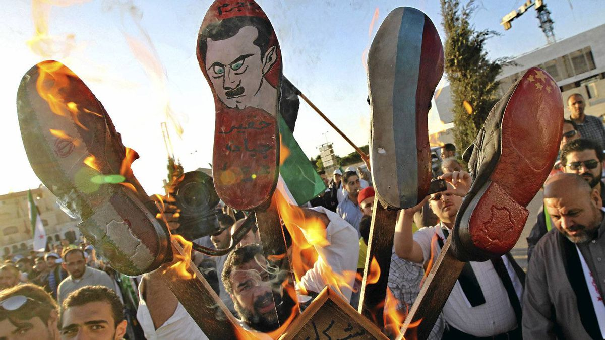 Syrian protesters living in Jordan burn shoes symbolizing Iran (L-R), Syrian President Bashar al-Assad, Russia and China during a protest against the killing of at least 108 people in the Syrian town of Houla last Friday, outside the Syrian embassy in Amman May 31, 2012.