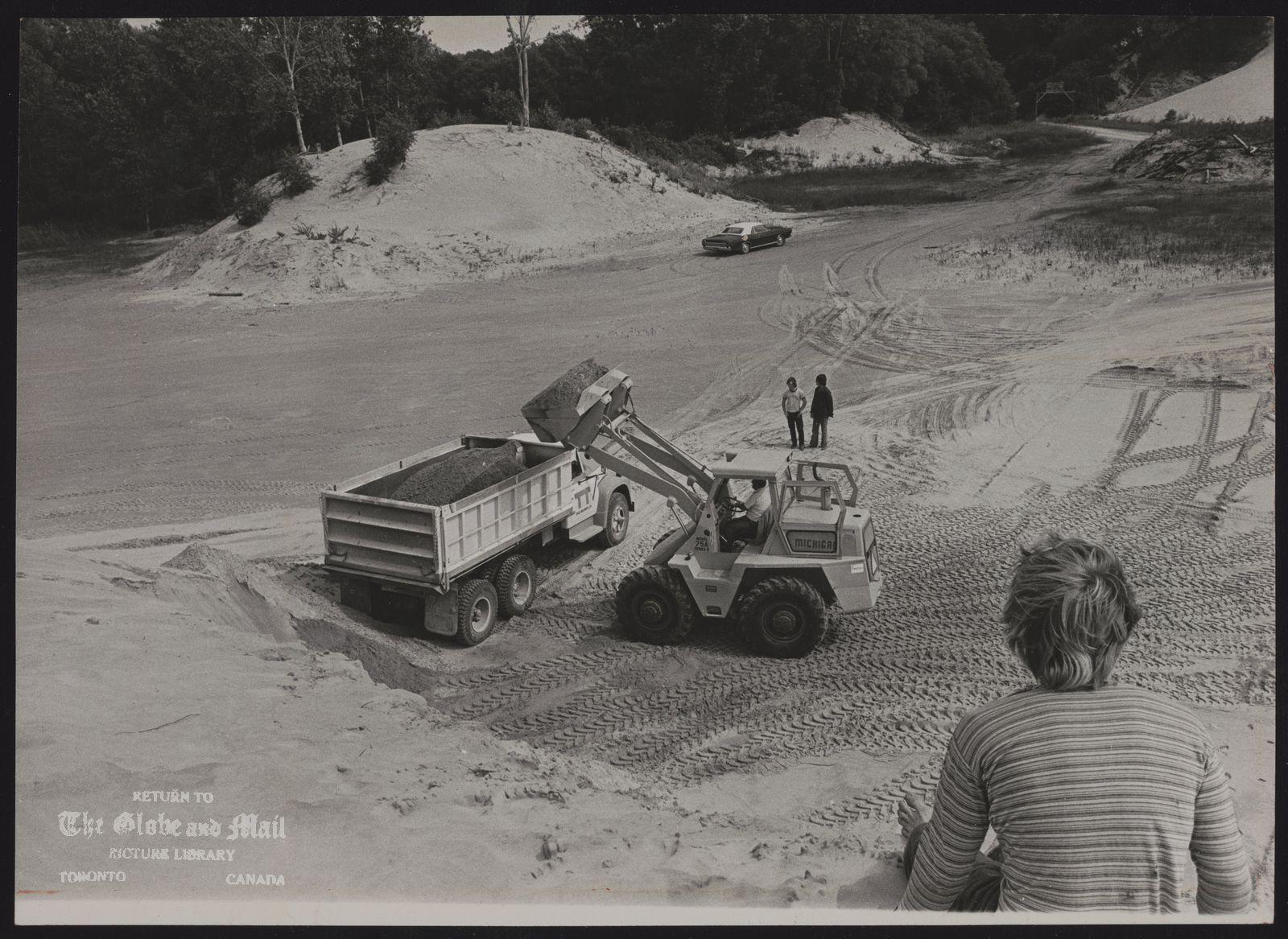 SANDBANKS PROVINCIAL PARK Ontario Front end loader fills truck with sand used forcement