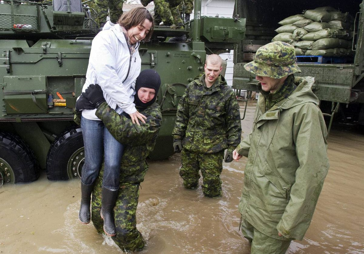 Soldiers from the 22nd Regiment, known as the VanDoos, help a reporter over the floodwaters in the streets od Saint Blaise, Que.