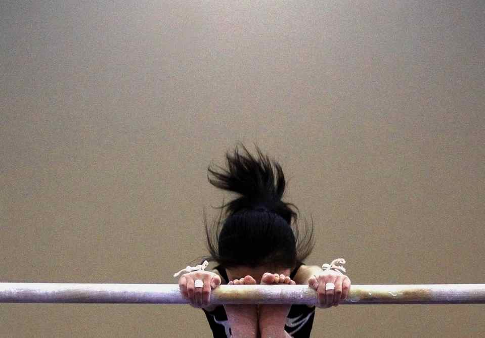A young gymnast hangs from an uneven bar during a gymnastics class.