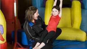 Go-Go Gymnastics founder Kara Hachey, left, instructs Sarah Beazley in a gymnastics class in Fredericton.