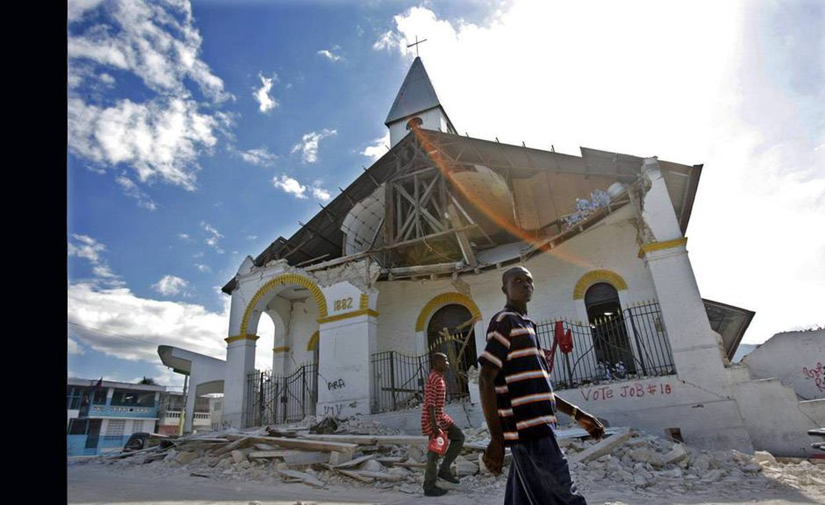 Survivors walk past a church destroyed in Tuesday's earthquake in Haiti's Capitol, Port-au-Prince Wednesday.