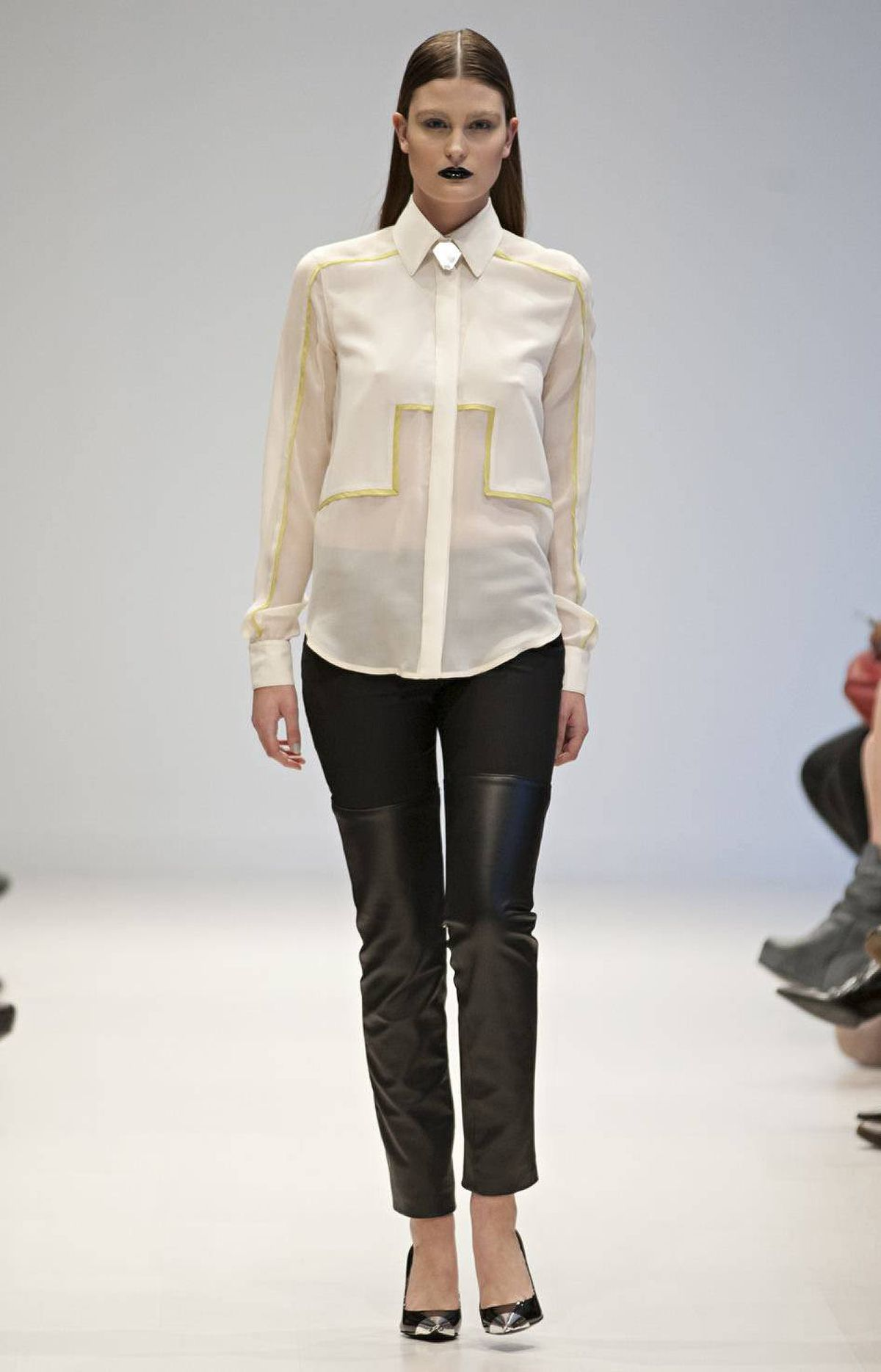 Graphic elements were present even in the jewellery, which was cool and understated, designed by Toronto's Ana Bogdanovic. (Yes, she made the silver toe caps on the stilettos, too.) Necklaces were often styled with button-up blouses in silk, most effectively this cream number with green piping.
