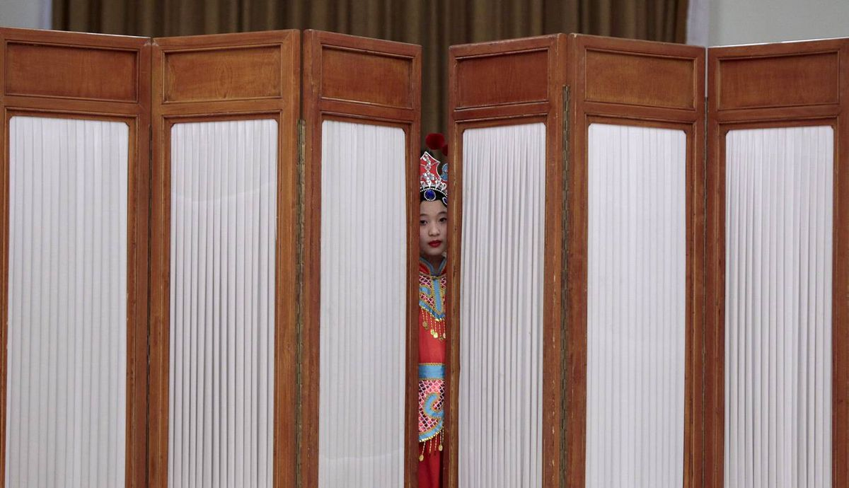 A girl looks out from behind a screen as she waits to perform at the Great Hall of the People in Beijing