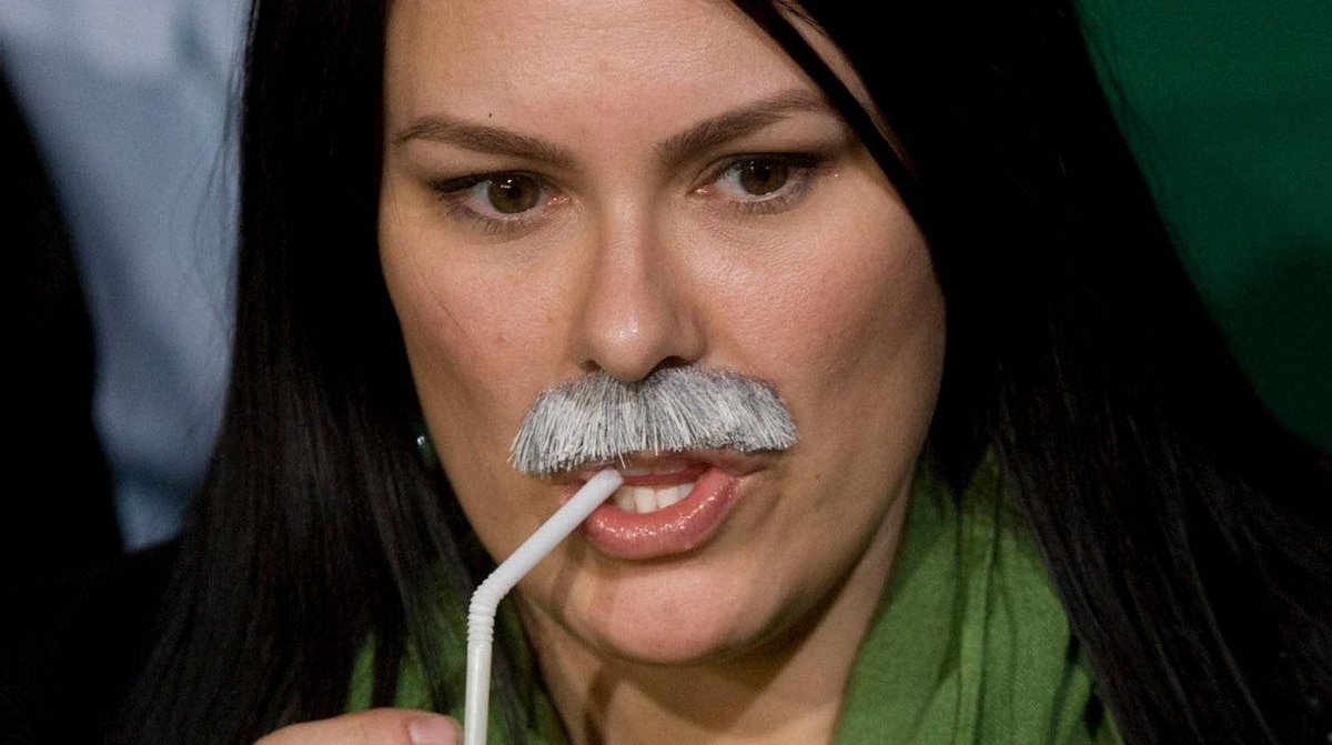 A New Democratic Party supporters sports a Jack Layton mustache as she takes part in their election event in Toronto on Monday, May 2, 2011.